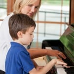Piano teacher teaching boy student
